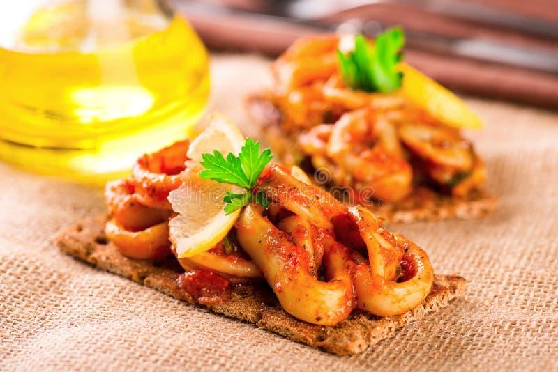 Aperitivo con los calamares y el limón picantes del tomate en tostada foto de archivo
