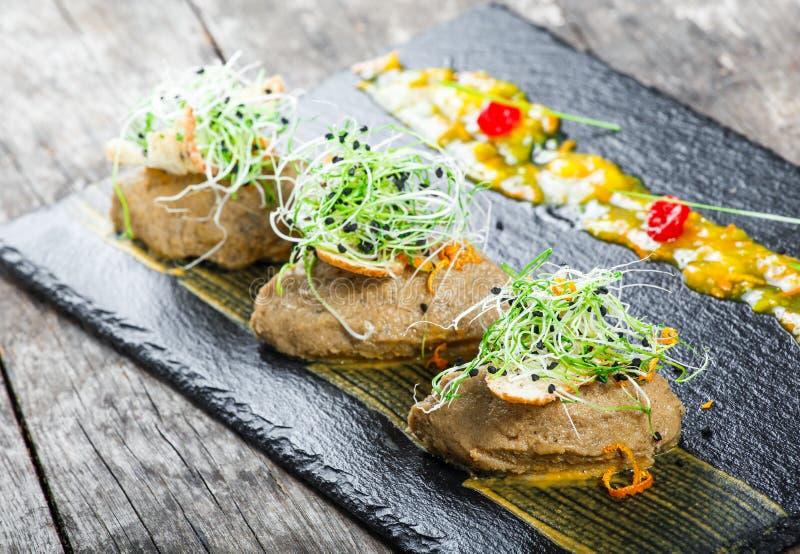 Aperitivo dal patè e dalla cipolla della carne sul fondo di pietra dell'ardesia sulla tavola rustica fotografia stock libera da diritti