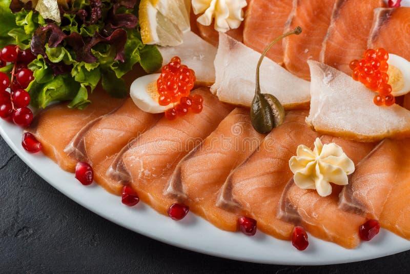 Aperitivo de los pescados de color salmón ligeramente salados adornados con el caviar, la lechuga y frezalis fotografía de archivo