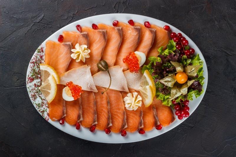 Aperitivo del pesce di color salmone leggermente salato decorato con il caviale, la lattuga e i frezalis fotografia stock libera da diritti
