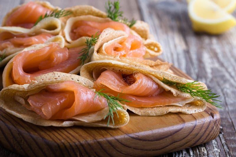 Aperitivo del salmone affumicato, crêpe farciti sul bordo di legno fotografia stock libera da diritti