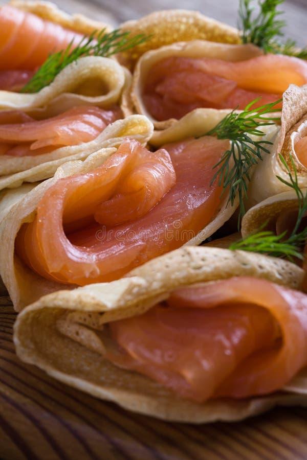 Aperitivo del salmone affumicato, crêpe farciti sul bordo di legno fotografie stock