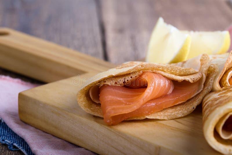 Aperitivo del salmone affumicato, crêpe farciti sul bordo di legno fotografia stock