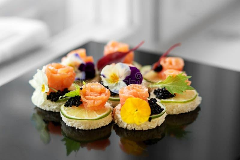 Aperitivo delicioso com salmões e as flores comestíveis Conceito para o alimento, restaurante, menu, restauração imagem de stock royalty free