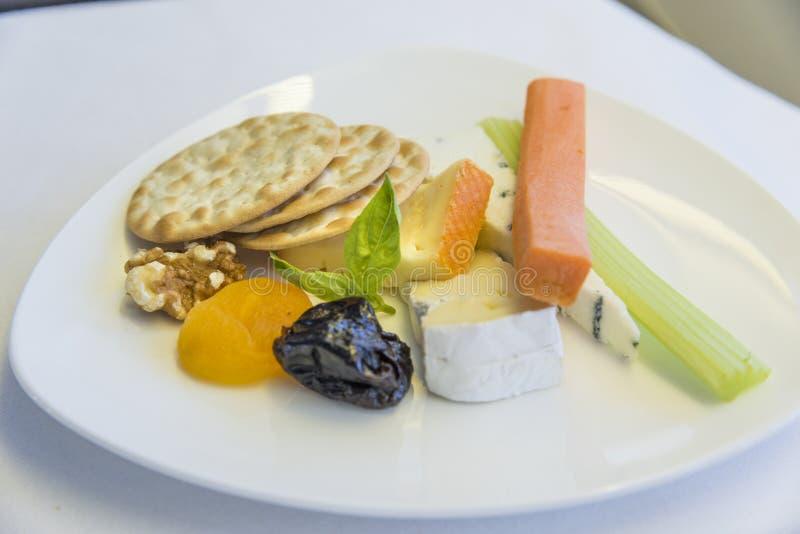 Aperitivo determinado de la comida de aviones en una bandeja, en una tabla blanca fotos de archivo