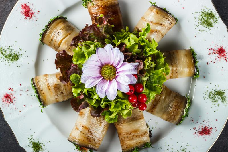 Aperitivo di melanzana farcita con il salmone salato decorato con lattuga ed il fiore immagini stock