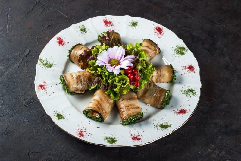Aperitivo di melanzana farcita con il salmone salato decorato con lattuga ed il fiore fotografia stock