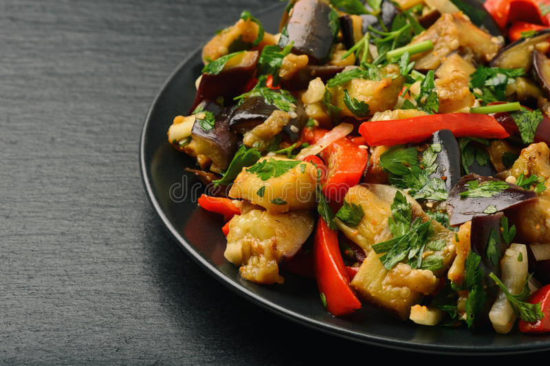Aperitivo - ensalada asiática con las berenjenas, la paprika y el ajo en fondo negro imagen de archivo libre de regalías