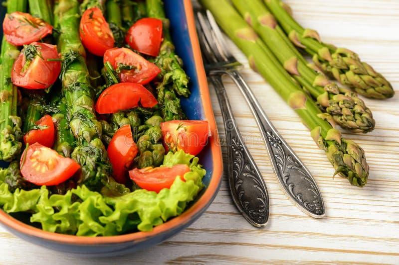 Aperitivo - ensalada vegetariana deliciosa con el espárrago, los tomates y la preparación verdes de la vinagreta fotografía de archivo libre de regalías