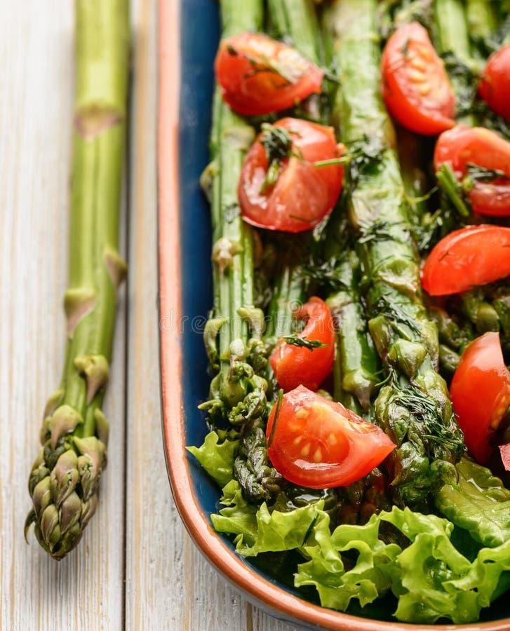 Aperitivo - ensalada vegetariana deliciosa con el espárrago, los tomates y la preparación verdes de la vinagreta fotos de archivo libres de regalías