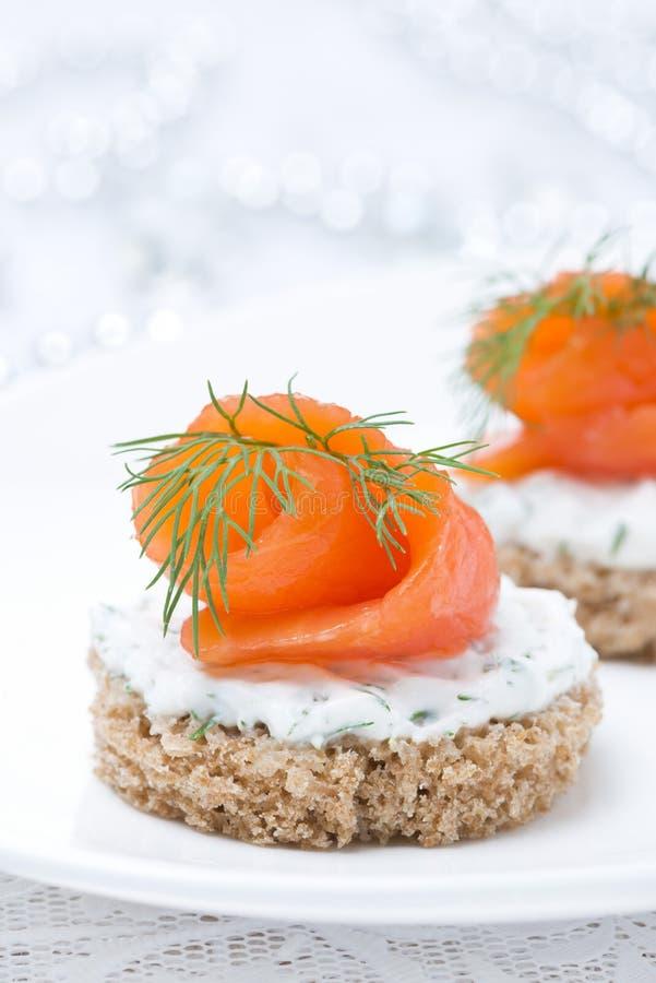 Aperitivo festivo - canape con il pane di segale, formaggio cremoso, salmone fotografia stock