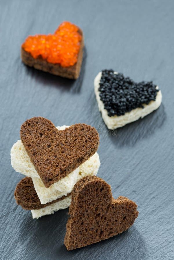 Aperitivo festivo - tueste con el caviar rojo y negro foto de archivo libre de regalías