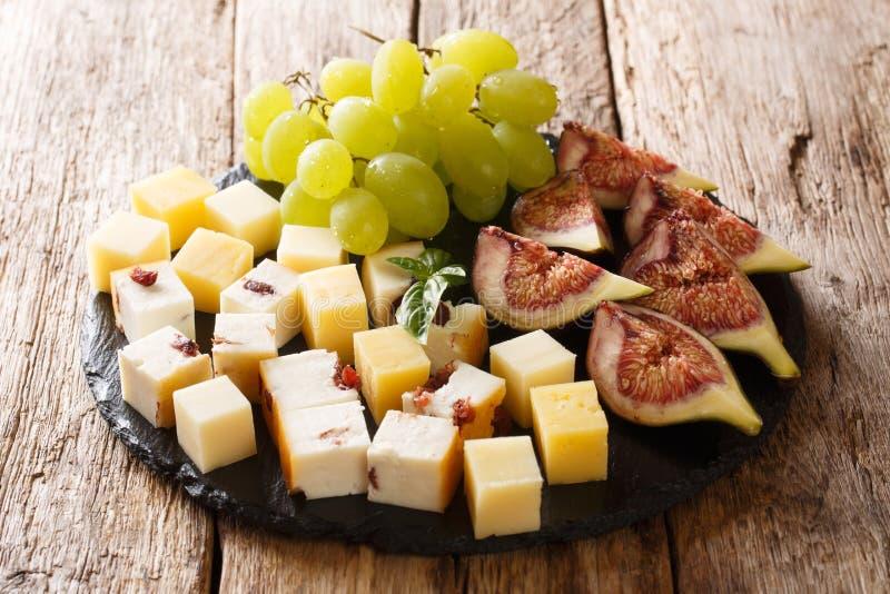 Aperitivo gastrónomo de los antipasti del diverso queso, de uvas frescas y del primer de los higos en un tablero de la pizarra ho imágenes de archivo libres de regalías