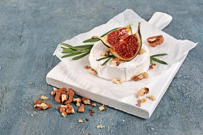 Aperitivo gourmet do queijo ou do camembert branco do brie com figos frescos, porcas e especiaria dos alecrins na placa de madeir fotografia de stock royalty free