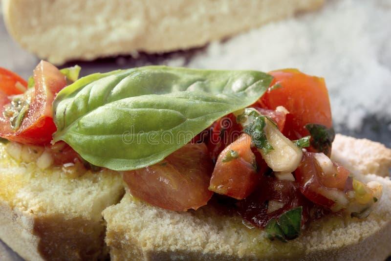 Aperitivo italiano Bruschetta con los tomates y la albahaca foto de archivo
