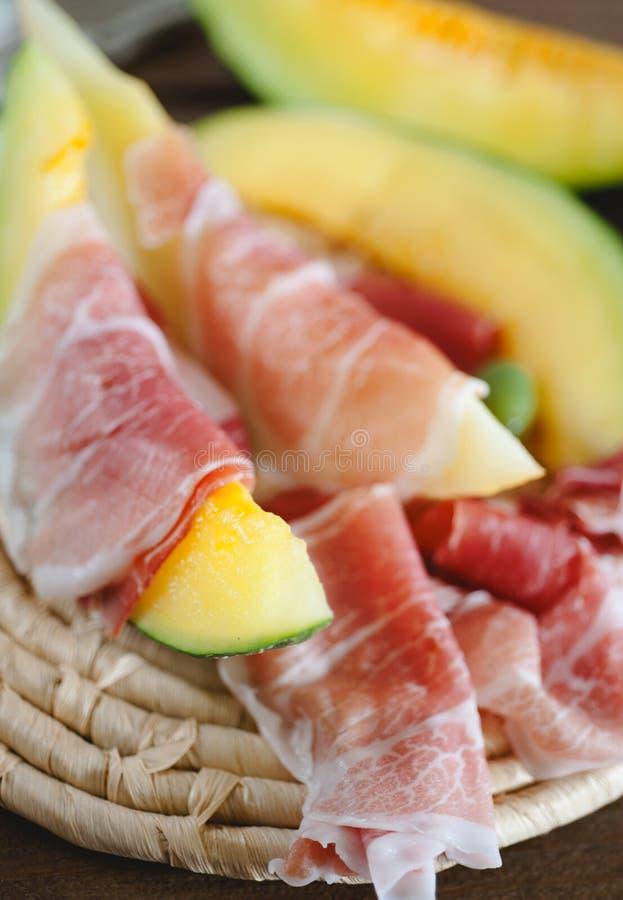 Aperitivo italiano - melón fresco y jamón de Parma delicioso fotografía de archivo