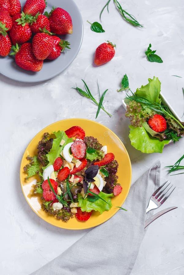 Aperitivo jugoso con la ensalada, fresas, queso y albahaca, y huevo curruscantes foto de archivo libre de regalías