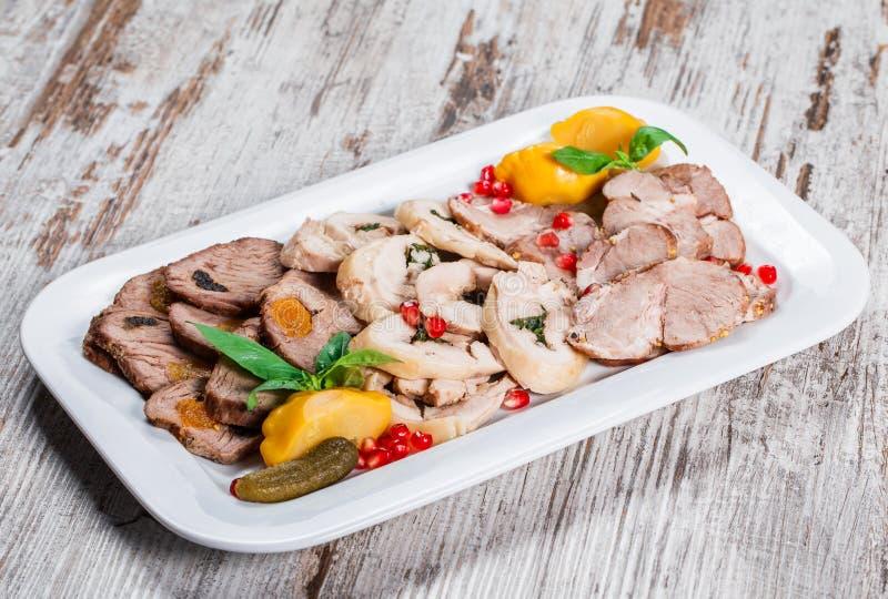 Aperitivo ordinato della carne, lingua di manzo, prosciutto, rotolo farcito del pollo, polpettone con pepe, verdi sul piatto sopr immagini stock