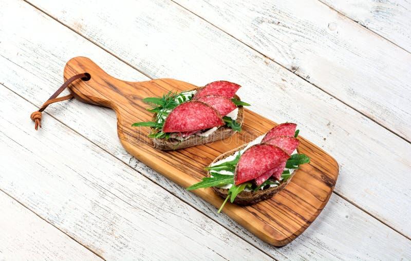 Aperitivo sabroso del salami picante fino cortado en el pan con queso e hierbas en una tabla de cortar con el espacio de la copia imágenes de archivo libres de regalías