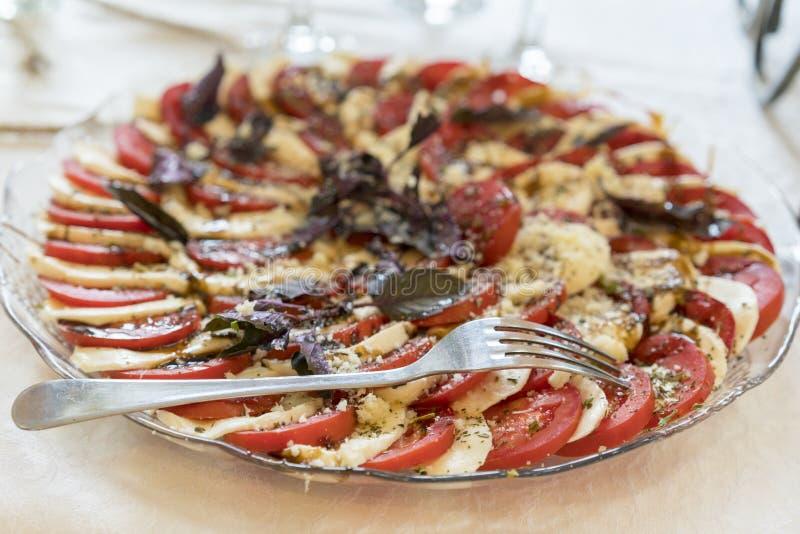 Aperitivo sano - insalata caprese con il pomodoro e la mozzarella, alimento italiano della dieta mediterranea immagini stock