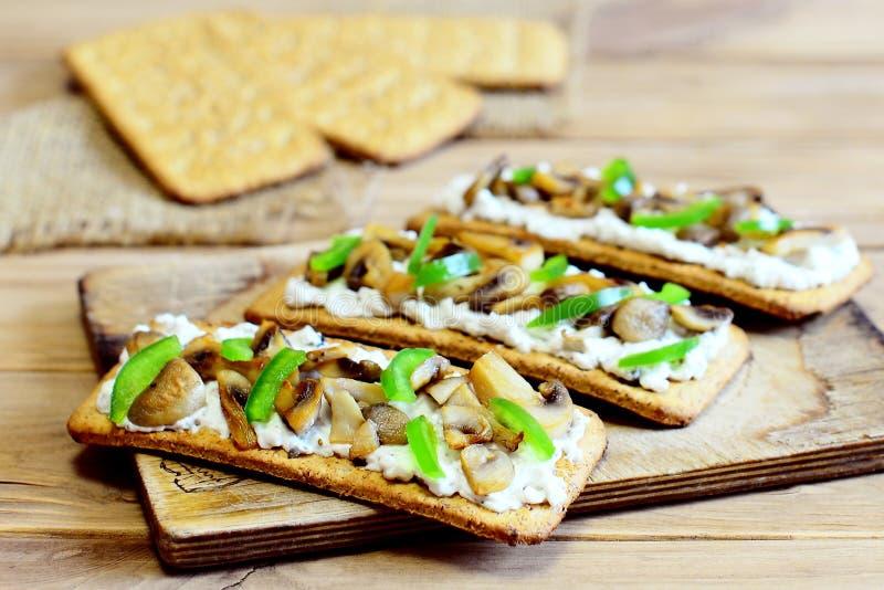Aperitivo saporito con i funghi fritti ed il peperone dolce verde fresco su un bordo di legno Spuntino vegetariano facile e calor immagine stock