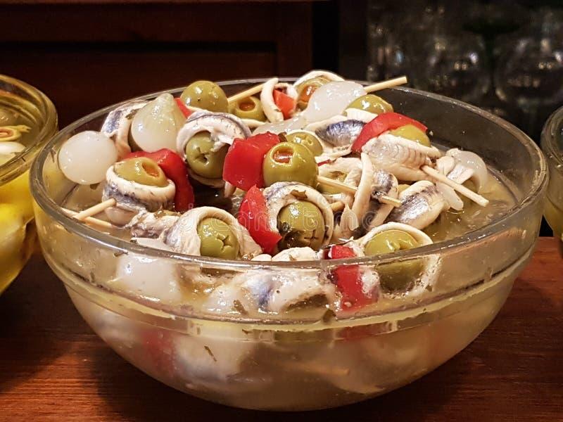Aperitivo típico con las aceitunas de la sardina y la pimienta roja imagenes de archivo