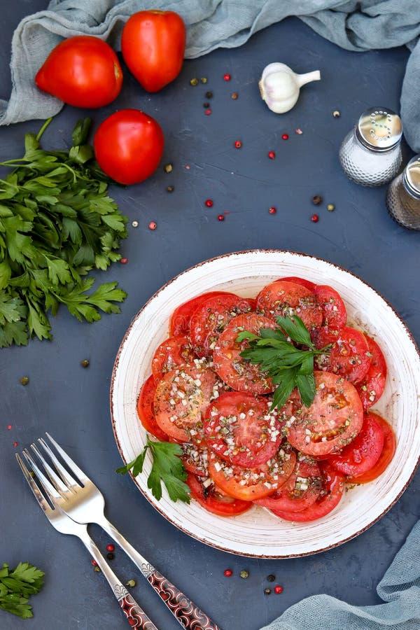 Aperitivo vegetariano de tomates con el ajo, perejil, vestido con la miel y el aceite de oliva situados en una placa en un fondo  foto de archivo libre de regalías