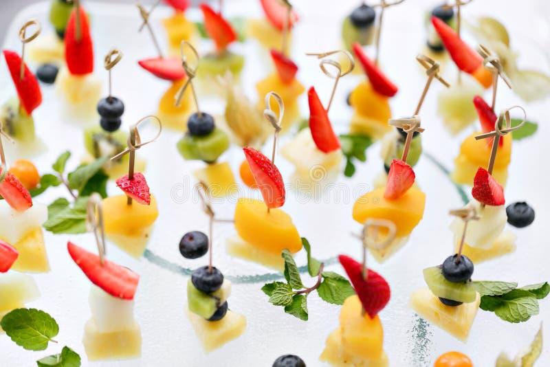 Aperitivos, comida gastrónoma - canape con queso y fresas, servicio de abastecimiento de los arándanos Foco selectivo, visión sup fotos de archivo libres de regalías