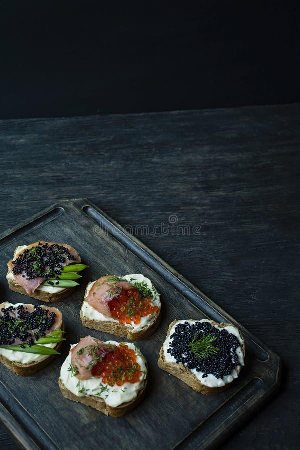 Aperitivos con el caviar rojo y el caviar negro en una tajadera oscura Primer Fondo de madera oscuro fotografía de archivo
