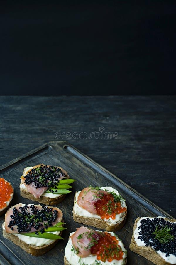 Aperitivos con el caviar rojo y el caviar negro en una tajadera oscura Primer Fondo de madera oscuro imágenes de archivo libres de regalías
