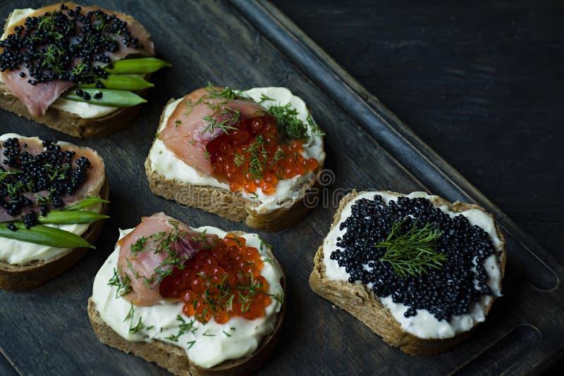 Aperitivos con el caviar rojo y el caviar negro en una tajadera oscura Primer Fondo de madera oscuro foto de archivo