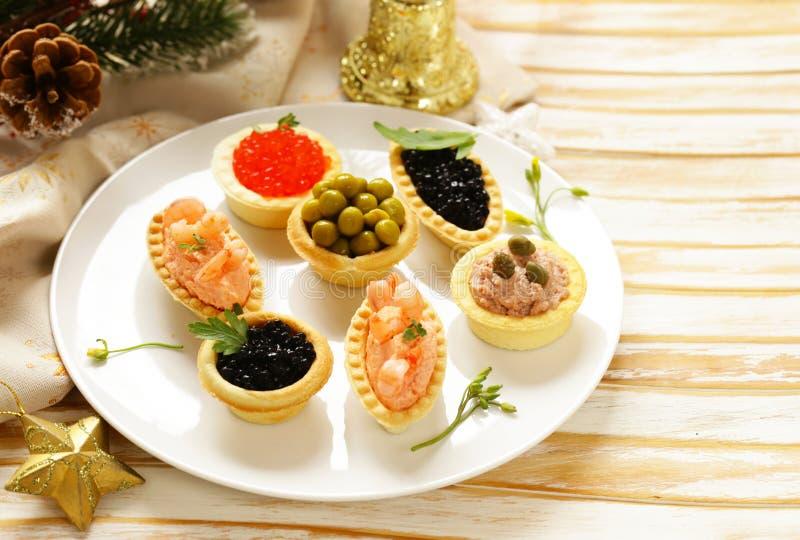 Aperitivos de la Navidad Pequeños tartlets con el caviar y la coronilla imágenes de archivo libres de regalías