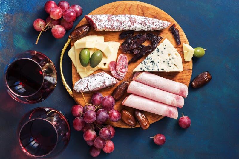 Aperitivos deliciosos com vinho tinto em um fundo azul Fruto, queijo, presunto, salsicha Vista superior, configuração lisa fotos de stock royalty free