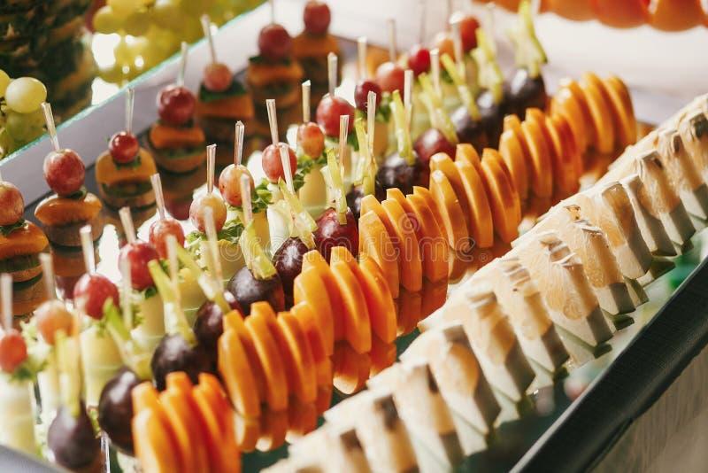Aperitivos deliciosos de las frutas, postres en soporte, tabla dulce moderna en la boda o fiesta de bienvenida al bebé Concepto d foto de archivo