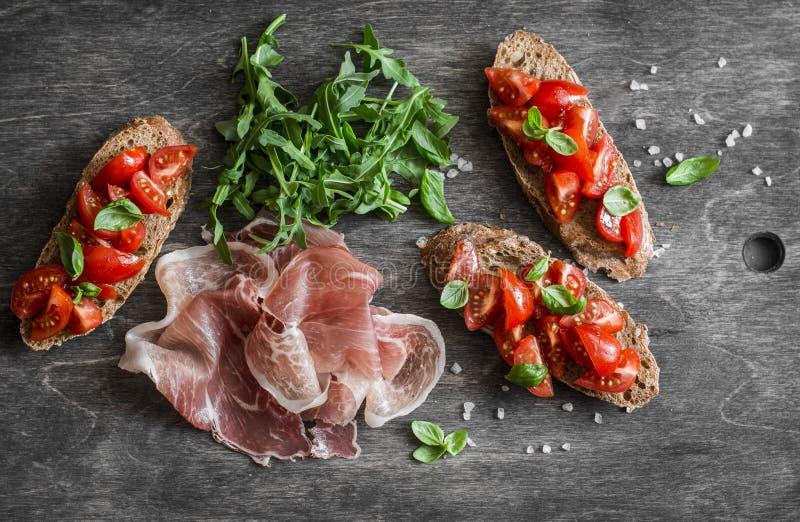 Aperitivos deliciosos para o vinho ou o petisco - bruschetta, proscutto e rúcula dos tomates de cereja Alimento mediterrâneo do e fotos de stock