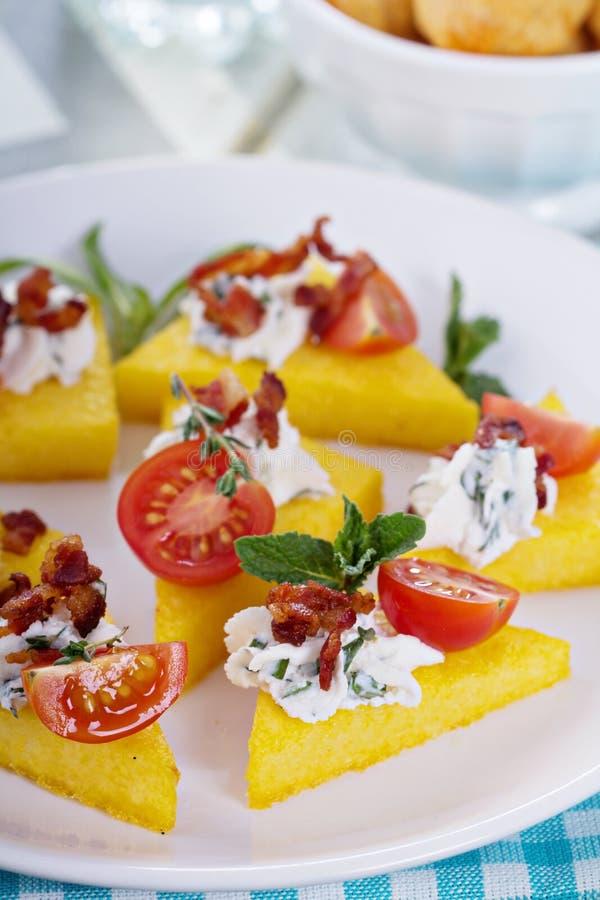 Aperitivos do Polenta com ricota e bacon fotografia de stock