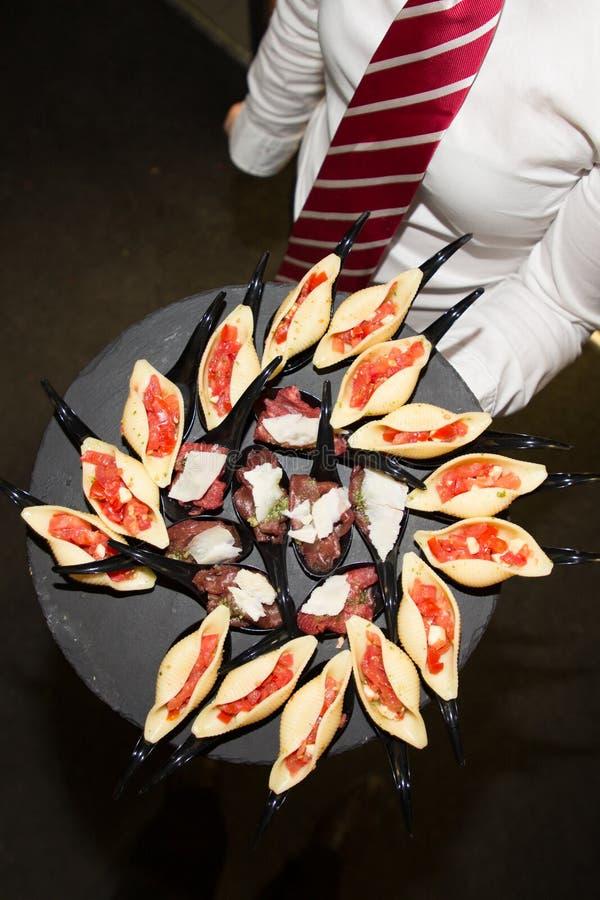 Aperitivos en un plato traído por el camarero foto de archivo libre de regalías