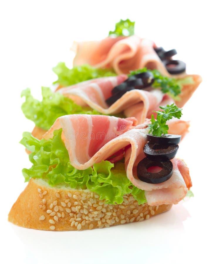 Aperitivos - fatias do pão com bacon imagens de stock