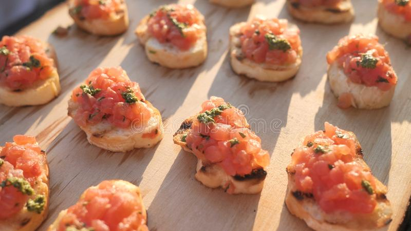 Aperitivos italianos sabrosos deliciosos del tomate, o bruschetta, en las rebanadas de baguette tostado, adornadas con albahaca n fotografía de archivo libre de regalías