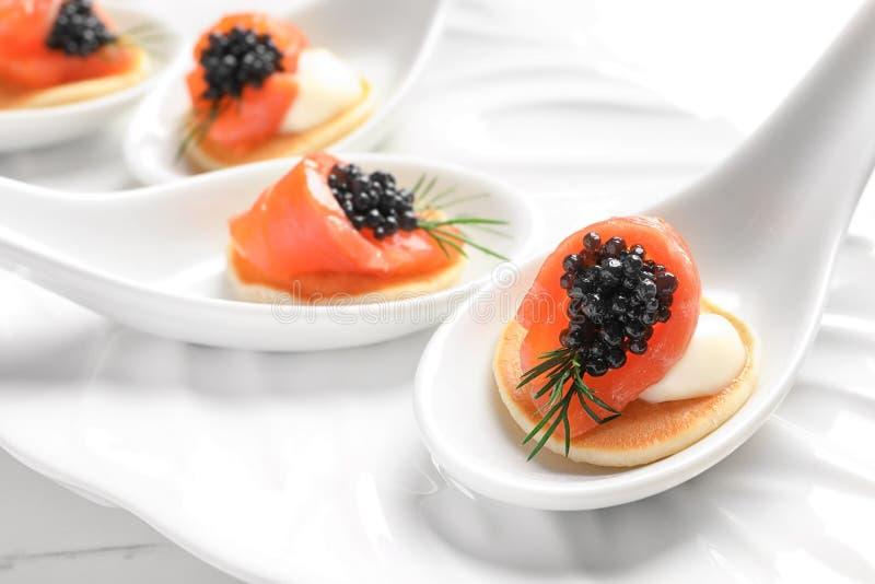 Aperitivos sabrosos con el caviar y los salmones negros imagen de archivo
