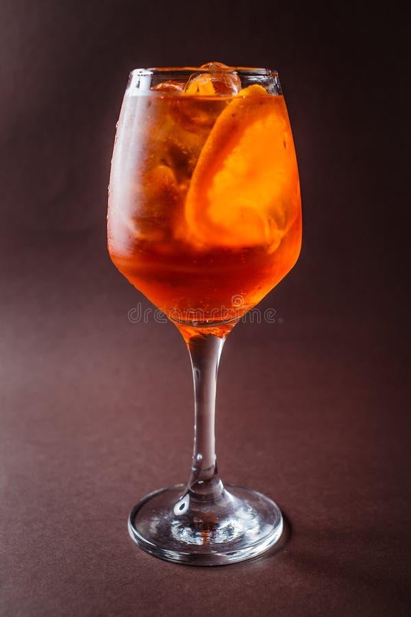 Aperol玻璃喷用在典雅的黑褐色backgro的桔子 免版税库存照片