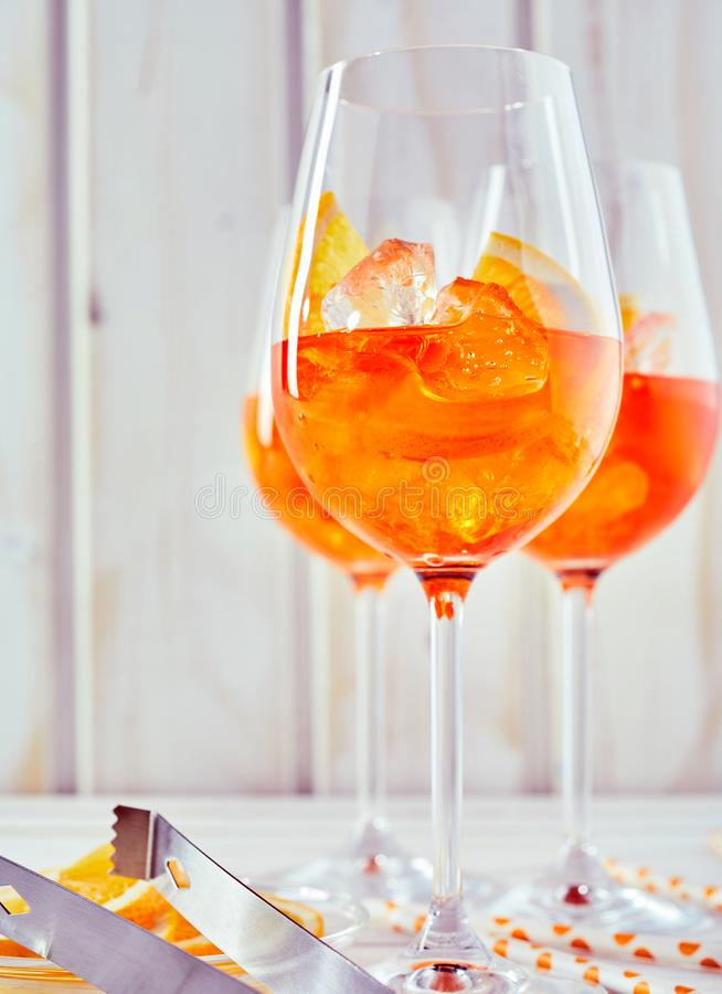Aperol orange spritz cocktails and equipment. A close up of aperol orange spritz cocktails, glasses and mixing equipment on a plain white timber background in royalty free stock image
