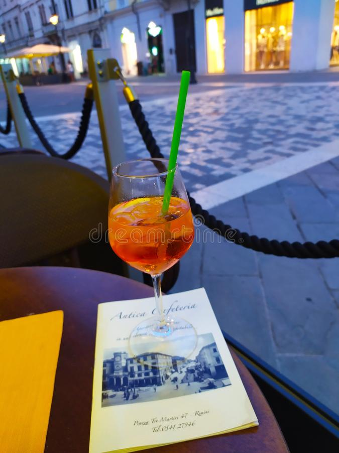 An Aperol shpritz goblet in the twilight. An Aperol shpritz goblet in the  warm twilight royalty free stock image