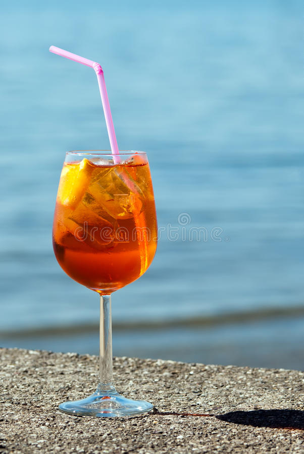 Aperol spritz. A glass aperol spritz stands by the water stock photography