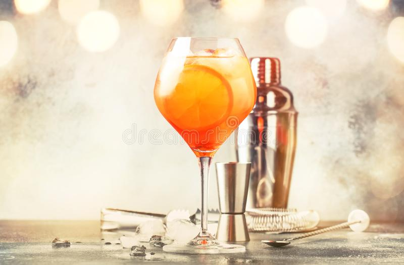 Aperol spritz cocktail in big wine glass with orange and ice, summer alcoholic cold drink, dark bar counter with steel bar tools, royalty free stock images