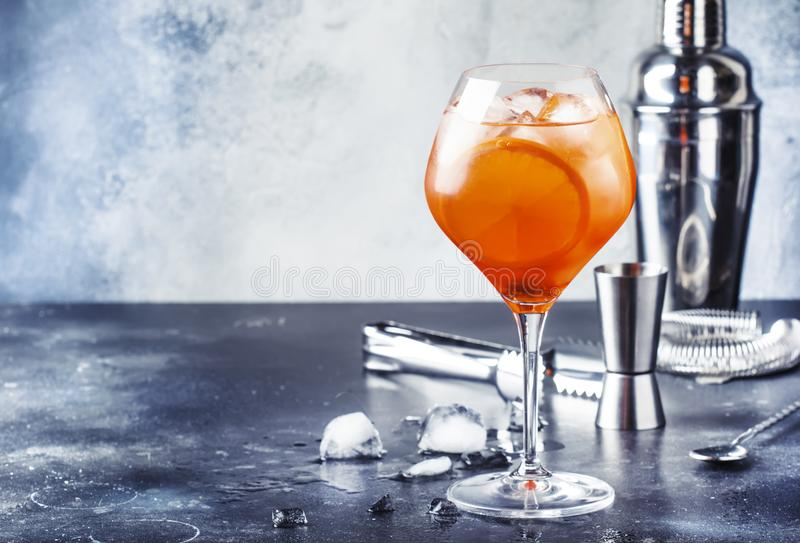 Aperol spritz cocktail in big wine glass with orange and ice, summer alcoholic cold drink, dark bar counter with steel bar tools, stock images