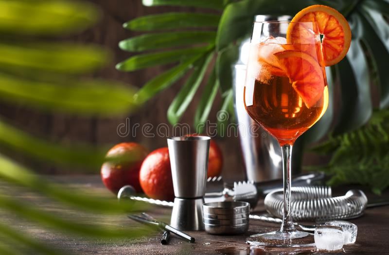 Aperol spritz cocktail in big wine glass with orange slices, summer cool fresh alcoholic cold beverage. Wooden bar counter. Background with tools, summer mood stock images