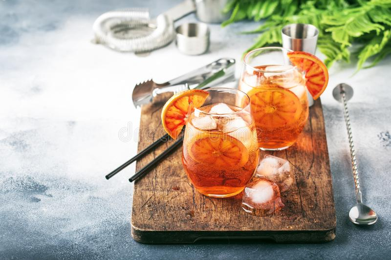Aperol spritz cocktail in wine glass with sparkling wine, liqueur, ice cubes and red orange - summer Italian low alcohol cold. Drink, gray stone bar counter royalty free stock image