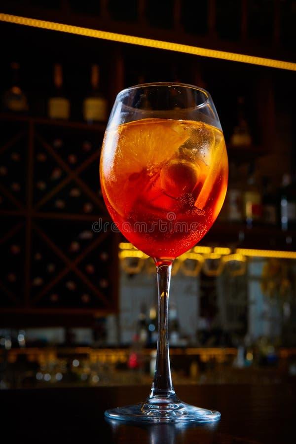 Aperol Spritz la bevanda alcolica del cocktail basata sul contatore della barra con i cubetti di ghiaccio e le arance fotografie stock