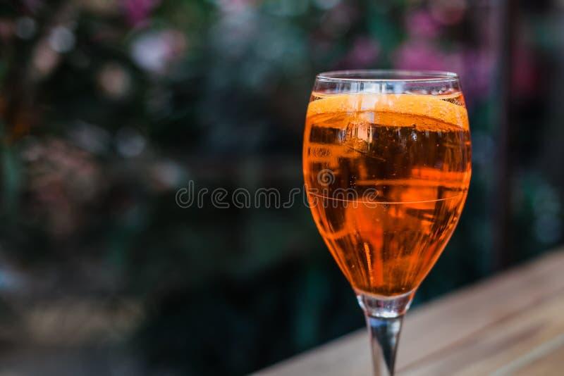 Aperol spritz o cocktail no vidro na tabela de madeira no fundo escuro no café fotografia de stock